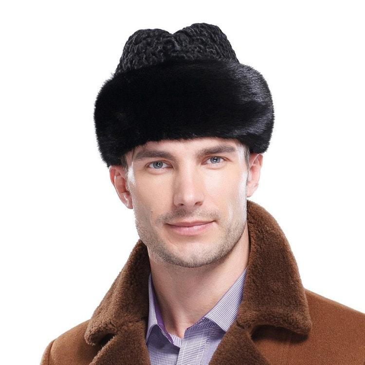 Мужчина в коричневом пальто и шапке из Каракуля