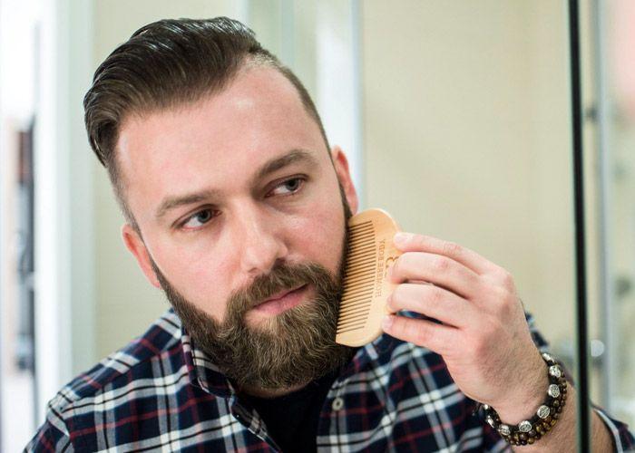Мужчина распределяет масло для бороды с помощью гребня
