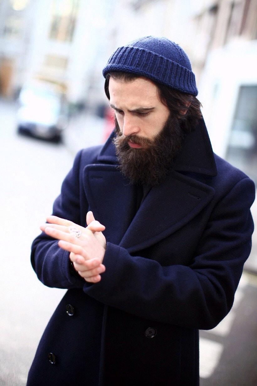 Мужчина в синем пальто и шапке с отворотом
